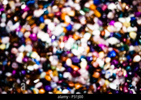 Colorful background with small stones. Abstract blurred background with colored rocks. Closeup image of decorative stones. Shiny precious small stones