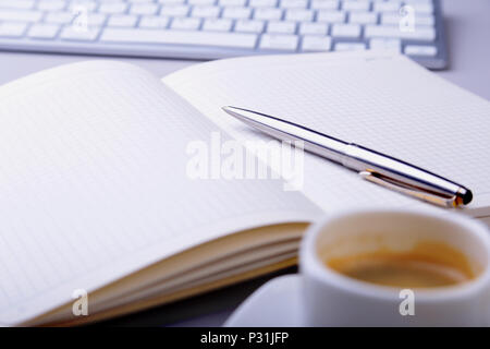 office table with notebook, computer keyboard,, cup of coffee, tablet pc. copy space. - Stock Photo