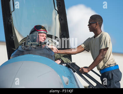 U.S. Air Force Senior Airman Christopher Tidline, a 354th Maintenance Squadron aircrew egress technician who is cross-utilized as a crew chief with the 354th Aircraft Maintenance Squadron, prepares Royal Canadian Air Force Capt. Michael Walker, an 18th Aggressor Squadron pilot, for a sortie Aug. 17, 2016, during RED FLAG-Alaska 16-3 at Eielson Air force Base, Alaska. This exercise provides unique opportunities to integrate various forces into joint, coalition and multilateral training from simulated forward operating bases. (U.S. Air Force photo by Staff Sgt. Shawn Nickel) - Stock Photo