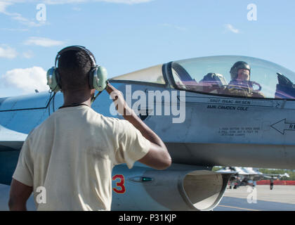 U.S. Air Force Senior Airman Christopher Tidline, a 354th Maintenance Squadron aircrew egress technician who is cross-utilized as a crew chief for the 354th Aircraft Maintenance Squadron, salutes Royal Canadian Air Force Capt. Michael Walker, an 18th Aggressor Squadron pilot, as he leaves for a sortie Aug. 17, 2016, during RED FLAG-Alaska 16-3 at Eielson Air Force Base, Alaska. This exercise provides unique opportunities to integrate various forces into joint, coalition and multilateral training from simulated forward operating bases. (U.S. Air Force photo by Staff Sgt. Shawn Nickel) - Stock Photo