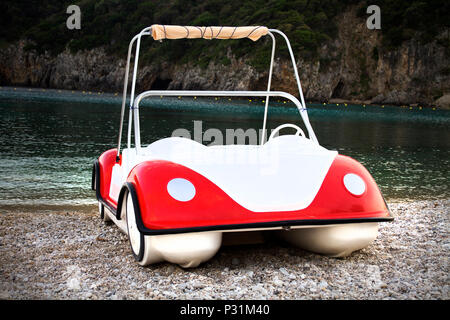 Quirky water boat with white, red paint. Parked in sandy, rocky seashore. It is settled in an island and used for the tourist for their travel in the  - Stock Photo