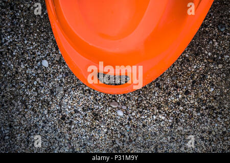A lifebouy rescue can in orange in the pebble, sandy ground of seashore in the beach of the island. Use by life guards to save people and tourist live - Stock Photo