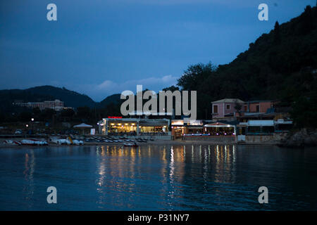Paleokastritsa, Cofru, Greece- MAY 10, 2018 An array of restaurants and diner in a stunning island. Chairs, motorboats are placed in sandy coast of se - Stock Photo