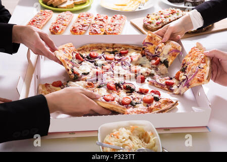 Friends Picking Slice Of Pizza From Box On Table - Stock Photo