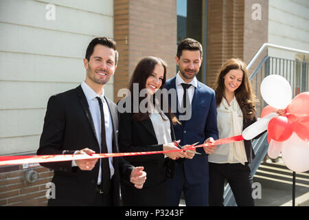 Happy Businesspeople Cutting Ribbon Outside Office Building - Stock Photo