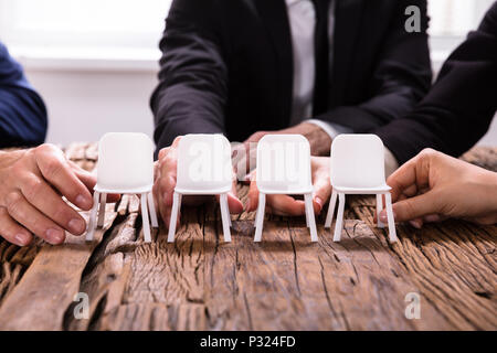 Close-up Of A Businesspersons's Hands Arranging Chairs In A Row - Stock Photo