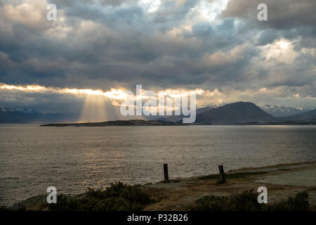 The sun finds an opening in the clouds and enlightens parts of Ushuaia. This photo is taken in Playa Larga, a popular day trip at the Beagle Channel. - Stock Photo