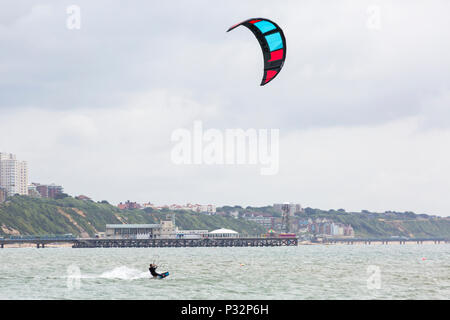 Branksome Chine, Poole, Dorset, UK. 17th June 2018. UK weather: breezy day at Branksome Chine beach, doesn't deter visitors going to the seaside. Wind surfer whizzing along with Bournemouth Pier in the background. Credit: Carolyn Jenkins/Alamy Live News - Stock Photo