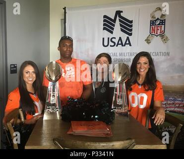 ENGLEWOOD, CO. –Spc. Nicholas Payne (middle left), Headquarters and Headquarters Company, 4th Combat Aviation Brigade, and his wife Samantha (middle right) pose with Denver Bronco Cheerleaders and Vince Lombardi trophies won by the Broncos in Super Bowl XXXII and XXXIII.  Payne participated in USAA's NFL Boot Camp at UCHealth Training Center Fieldhouse August 25, 2016. - Stock Photo