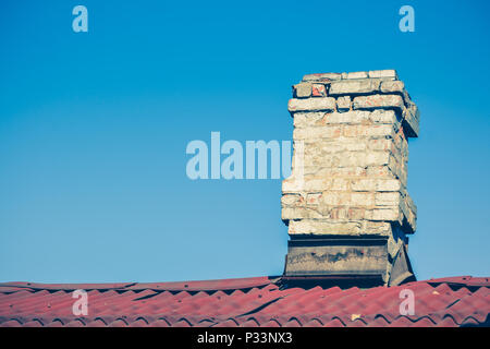 old brick chimney on the roof for the smoke against the clear sky - Stock Photo