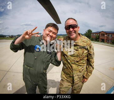 U.S. Army Chief Warrant Officer 3 Jason Richards, an OH-58D Kiowa Warrior pilot with 1st Squadron, 17th Cavalry Regiment, swaps flag patches with a South Korean pilot at an airfield in Yongin, South Korea, Aug. 29, 2016. (U.S. Army photo by Staff Sgt. Ken Scar) - Stock Photo