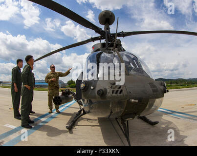 U.S. Army Chief Warrant Officer 3 Jason Richards, an OH-58D Kiowa Warrior pilot with Ist Squadron, 17th Cavalry Regiment, shows three South Korean pilots his aircraft at an airfield in Yongin, South Korea, Aug. 29, 2016. (U.S. Army photo by Staff Sgt. Ken Scar) - Stock Photo