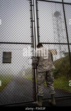 Airman 1st Class Kevin Plunkett, a radio frequency transmissions systems technician with the Hawaii Air National Guard's 169th Air Defense Squadron, unlocks the gates to Mt. Ka'ala Air Force station (AFS), Aug. 12, 2016, Oahu, Hawaii. Mt. Ka'ala AFS sits atop the highest point on the island of Oahu and houses the 169th ADS's radar equipment, which is used to monitor the airspace around the Hawaiian Islands. (U.S. Air Force photo by Tech. Sgt. Brandon Shapiro) - Stock Photo