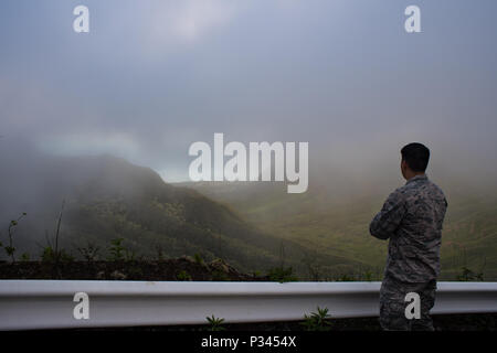 Airman 1st Class Kevin Plunkett, a radio frequency transmissions systems technician with the Hawaii Air National Guard's 169th Air Defense Squadron, looks out over the island of Oahu from the Ka'ala Air Force Station's main access road, Aug. 12, 2016, Oahu, Hawaii. The Hawaii Air National Guard oversees the monitoring of the airspace around the Hawaiian Islands at Wheeler Army Airfield, Oahu, Hawaii. (U.S. Air Force photo by Tech. Sgt. Brandon Shapiro) - Stock Photo