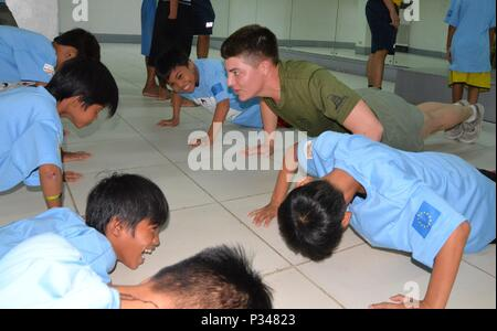 MANILA, Republic of the Philippines (June 13, 2018) US 7th Fleet Sailors and Marines visit Museo Pambata, a local children's' museum, and give out sporting goods and candy as they they play football with local street kids. More than 40 members of the U.S. 7th Fleet staff are currently embarked on USNS Millinocket (T-EPF 3), visiting several countries in the Indo Pacific in support of a theater security cooperation patrol. (U.S. Navy photo by Mass Communication Specialist 1st Class Chris Krucke /Released) - Stock Photo