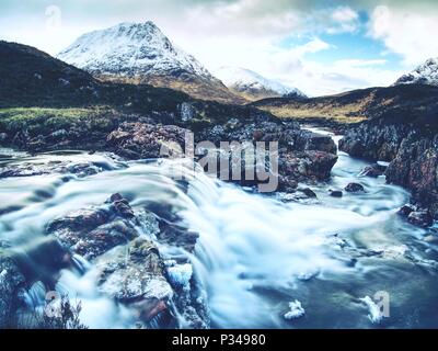 Pools and majestatic waterfalls belllow snowy mountains. Blue water mirrorong blue cloudy sky - Stock Photo