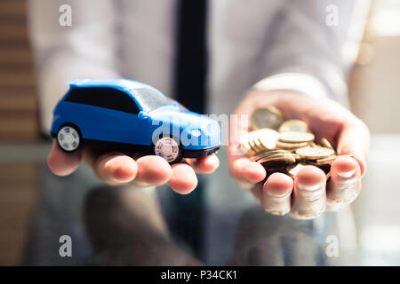 Close-up Of A Businessperson's Hand Holding Small Blue Car And Golden Coins - Stock Photo