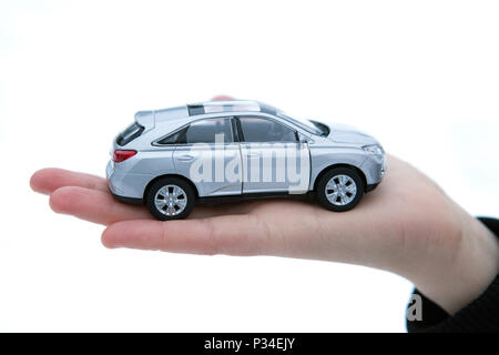 girl holds in her hand model of car closeup - Stock Photo