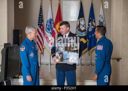 NASA astronauts Mark Vande Hei (left) and Joe Acaba (right) present Col. Jerry Farnsworth (center), chief of staff, Arlington National Cemetery and Army National Military Cemeteries, with a framed Expedition 54 patch in the Memorial Amphitheater Display Room at Arlington National Cemetery, Arlington, Virginia, June 15, 2018. The patch was flown abroad the International Space Station (ISS) during Expeditions 53/54. They also presented an ANC Employee patch to Col. Farnsworth and presented a Tomb Guard Identification Badge to Col. Jason Garkey, regimental commander, 3d U.S. Infantry Regiment (Th - Stock Photo