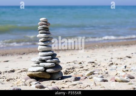 stones pyramid on the beach - Stock Photo