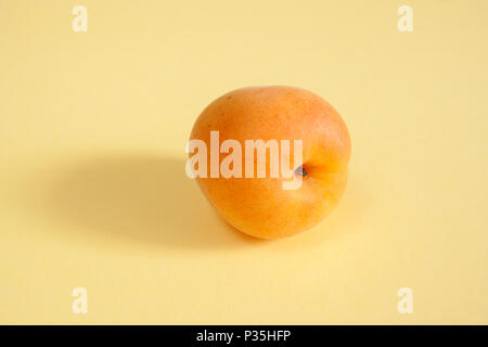 Heap of apricots in round bright terracotta bowl and near it on pink pastel background. - Stock Photo