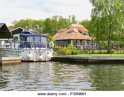 A motorboat moored by a riverside cottage with a thatched roof on the norfolk broads in england uk - Stock Photo