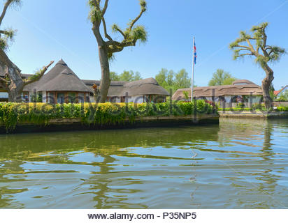 A riverside home with a thatched roof in the norfolk broads national park in england uk - Stock Photo