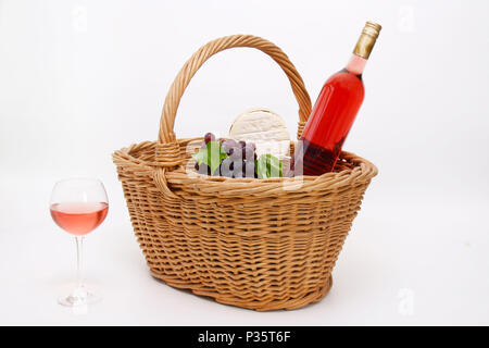 A basket filled with wine grapes, cheese and a bottle of Red wine - Stock Photo