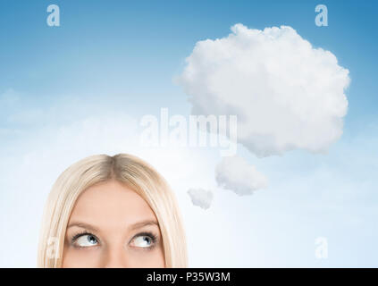 Close up of blonde woman looking up towards blank thought bubble with copy space - Stock Photo