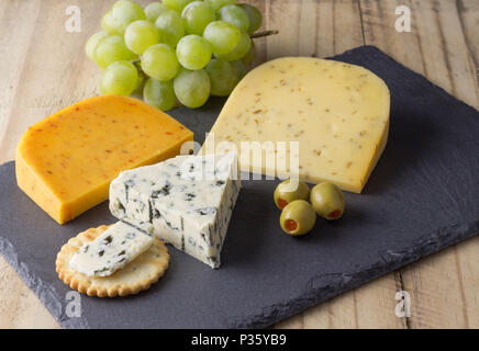 Cheese board with three cheeses, gouda with pimento, gouda with cumin seeds and roquefort blue cheese close up on rustic wooden background - Stock Photo