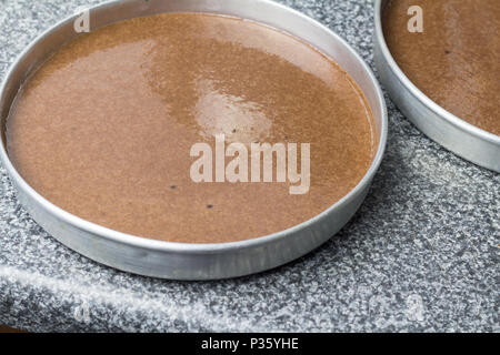 Cake pan with chocolate batter close up on kitchen counter top - Stock Photo