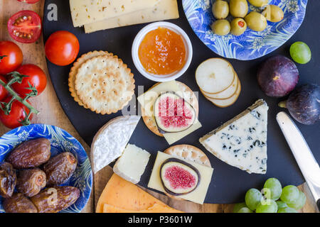 Cheese board close up with assortment of cheese, crackers, fruit and olives close up top view - Stock Photo