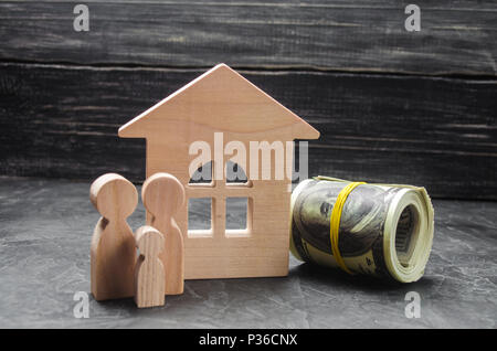 Wooden figures of the family stand near a wooden house and collapsed money. Buying and selling a house. Good life, moving to new apartments. Realtor s - Stock Photo
