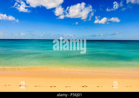 Idyllic afternoon at the beach in Barbados (Caribbean island): Nobody, white sand, clear turquoise water with waves and a sunny blue sky white clouds. - Stock Photo