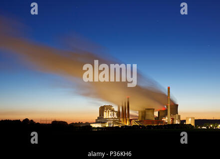 A large brown coal power station with night blue sky and very long steam cloud. - Stock Photo