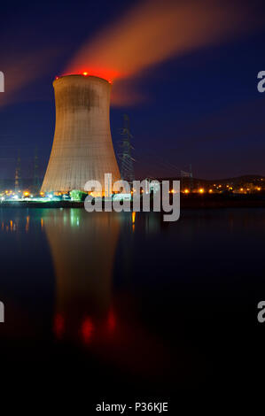 Night shot of a large nuclear power plant close to a river with blue night sky. - Stock Photo