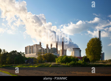 A brown coal power plant with lots of steam in the evening. - Stock Photo