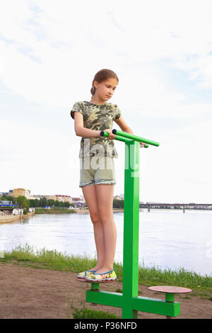 A teenage girl performs a workout on a disc simulator mounted on the river bank. In the background - city landscape - Stock Photo