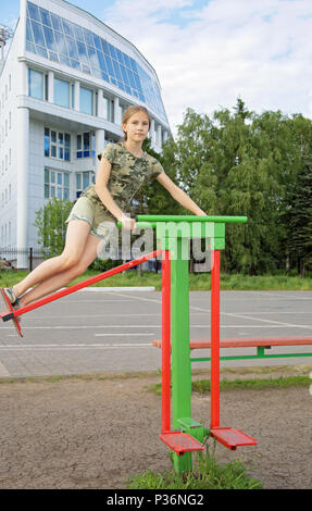 Teen girl trains on a swinging simulator installed in the Park. In the background-a modern building - Stock Photo