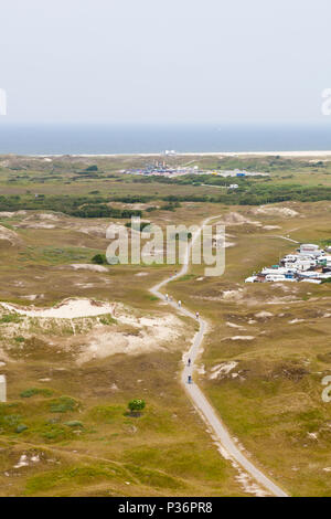 Aerial view of a footpath in between overgrown sand dunes in Norderney, Germany. The beach in the background. - Stock Photo