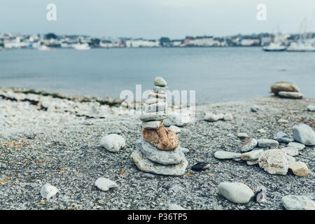 Stones pyramid on pebble beach symbolizing stability, zen, harmony, balance. Shallow depth of field with city on the background - Stock Photo