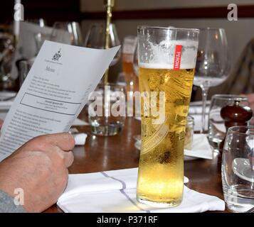 Pub menu in a man's hand and a pint glass of Peroni lager in a traditional English pub - Stock Photo