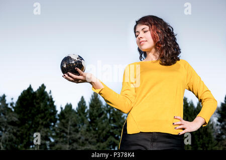 The whole world in her hand: Young woman in stylish yellow pullover holding earth in her hand in front of sky and trees. Save the earth concept. - Stock Photo