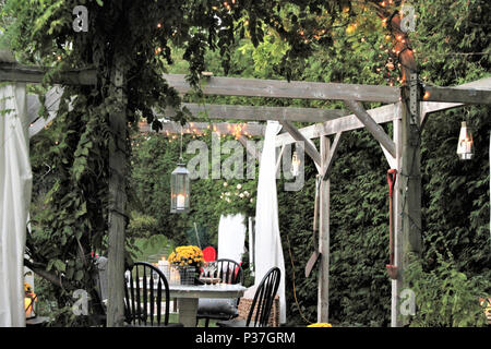Outdoor dining area with overhead arbour, greenery and lights - Stock Photo