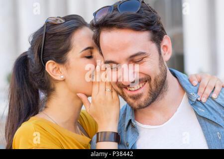 Woman is whispering a secret into his boyfriends ear - Stock Photo