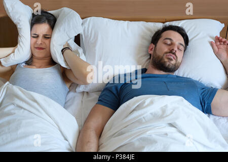 Stressed woman covering ears with a pillow as she is annoyed by the snoring of her boyfriend - Stock Photo