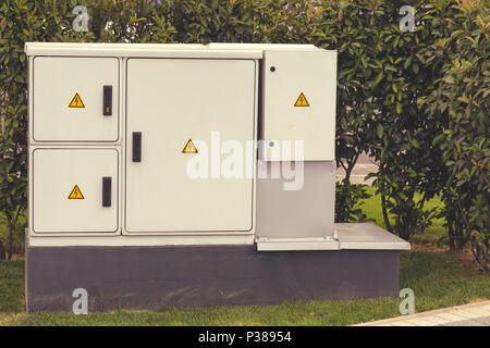 Outdoor plastic electrical cabinet with warning signs. An electrical enclosure is a cabinet for electrical or electronic equipment to mount switches,  - Stock Photo