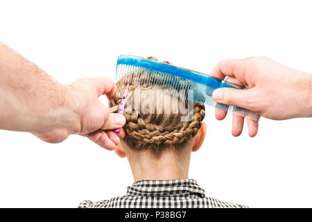 Male hands make a hairstyle for a little girl with a comb and a hair clip, isolated on a white background, first person view - Stock Photo