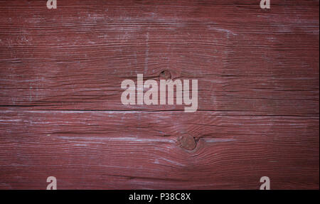 Close-up of an old and faded wood board wall painted in red with vignette - Stock Photo