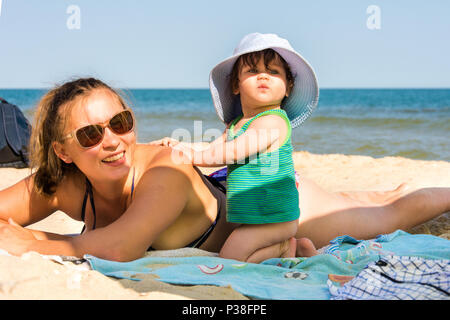 A super-fantastically beautiful girl on a sea beach eats and smiles - Stock Photo